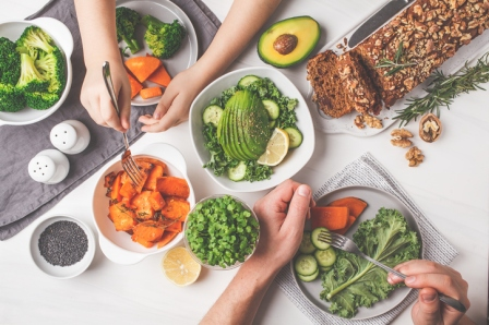 Healthy vegan food lunch, top view. Vegetarian dinner table, people eat healthy food. Salad, sweet potato, vegan cake, vegetables on white background.